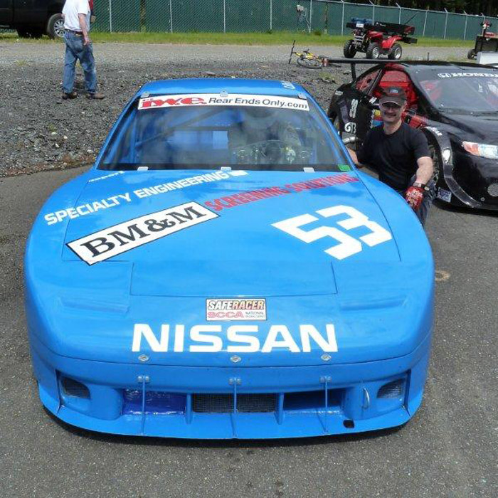 Collin Jackson posing in his #53 blue Nissan 240SX race car