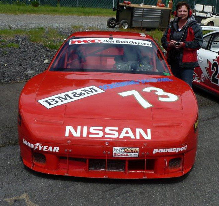 Dave Humprey posing in his #73 red Nissan 240SX race car